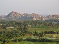 Green fields and distant view of Hampi, ancient town and travel destination in Karnataka, India.