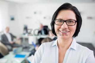 Ältere Geschäftsfrau als Chefin lächelt freundlich