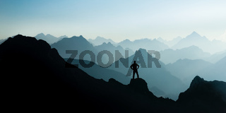 Spectacular mountain ranges silhouettes. Man reaching summit enjoying freedom.