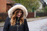 young woman wearing hooded winter coat playing coy