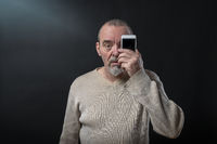 old man does not understand his smart phone
