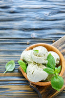 Balls of ice cream with basil in bowl.