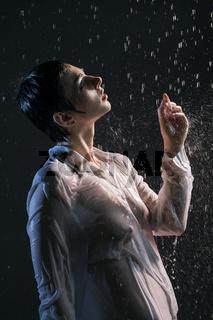 Brunette in wet shirt under water in the dark
