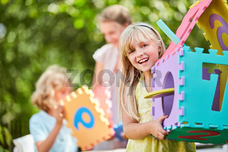 Mädchen steht glücklich mit Puzzle Traumhaus
