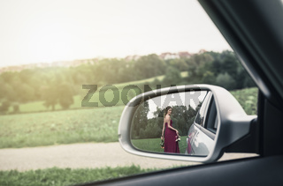 Elegant woman seen in the rearview mirror of car