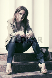 Sad young fashion woman sitting on the mall steps