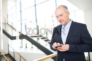 Älterer Geschäftsmann schreibt eine SMS