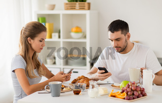 couple with smartphones having breakfast at home