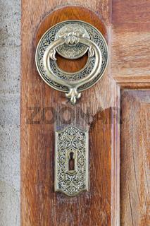 Closeup of antique copper ornate door knocker over an aged wooden door