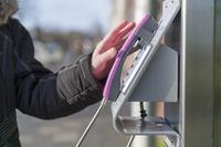 Die Hand einer Frau greift zum Hörer eines öffentlichen Telefons.