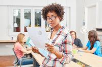 Multikulturelle Frau als Entrepreneur liest Dokument