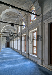 Passage in Nuruosmaniye Mosque  with columns, arches and floor covered with blue carpet lighted by side windows located in Shemberlitash, Fatih, Istanbul, Turkey