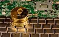 Ethereum coin on a keyboard with printed circuit board