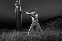 Monochrome shots of a male boxer training with a punching bag ou