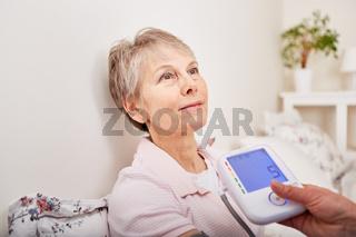 Bei einer Seniorin wird Blutdruck gemessen