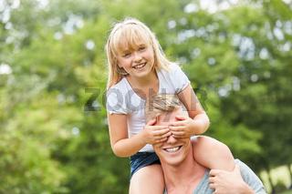Mädchen hält ihrem Vater die Augen zu