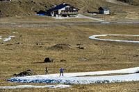 Skilangläufer trainieren aufimprovisierter Loipen aus Kunstschnee im Gras, Frankreich