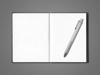 Blank open notebook and pen isolated on dark grey