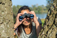 Woman looking through binoculars  near trees