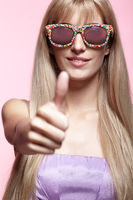 Young blonde smiling  woman with fun candy glasses and thumb up on pink background