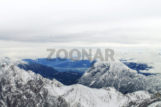 View of a mountain range with snow and clouds