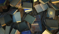 Many old and ancient books, spread over a wooden surface.