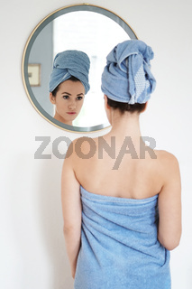 young woman wrapped in towel looking into mirror