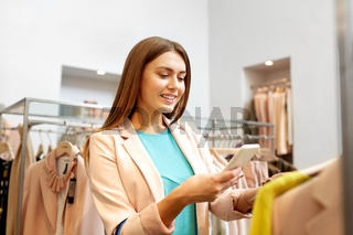 happy woman using phone app at clothing store