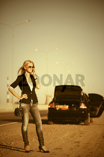 Fashion woman calling on cell phone next to broken car