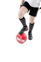 Junges Kind in Fußballkleidung hält einen Ball