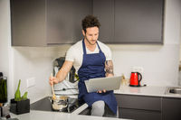 Man in kitchen, cooking and reading on laptop PC