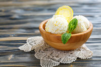 Balls of lemon ice cream in a wooden bowl.
