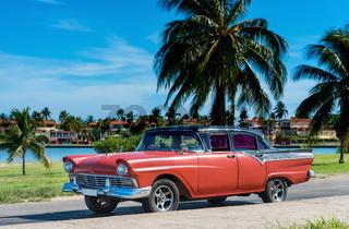 Amerikanischer roter Oldtimer parkt am Strand unter Palmen in Varadero Cuba - Serie Cuba Reportage