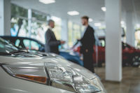 Auto showroom, dealer talking with buyer.