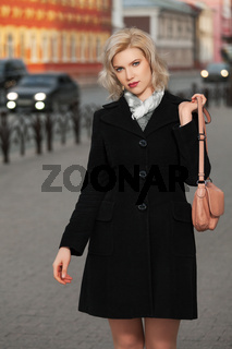 Fashion blond woman in black coat walking in city street