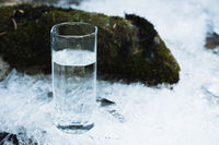 Transparent glass glass with drinking mountain water in winter stands on an icy crust against the background of a clean, frosty river bank. The concept of drinking mountain drinking mineral water and the production of mineral ecologically clean drinking w