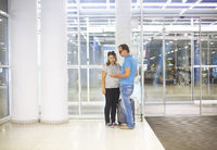 Pregnant couple with suitcase at airport or station