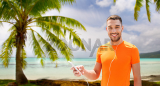man with smartphone and earphones over beach
