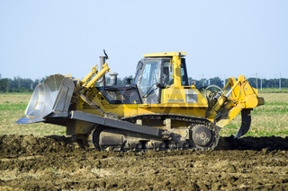 The yellow tractor with attached grederom makes ground leveling.