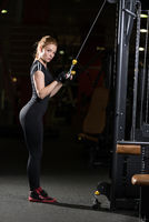 Woman at the sport gym doing arms exercises on a machine