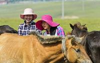 Zwei junge mongolische Frauen mit modischen Hüten zwischen Pferden, Mongolei
