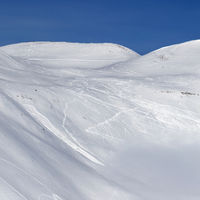 Snowy slope for freeriding with traces of skis, snowboards and avalanches