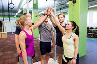 group of happy friends making high five in gym