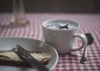 kleines Paperschiff in einer Tasse