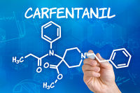 Hand with pen drawing the chemical formula of Carfentanil