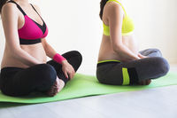 Two young pregnant women doing yoga exercises
