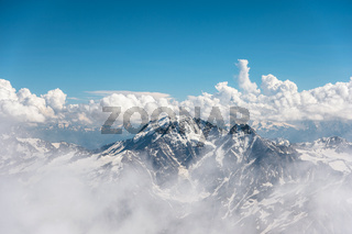 Dark blue sky with clouds on the rocky peaks of the mountains covered with glaciers and snow