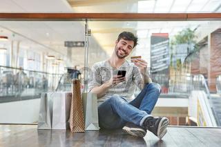 Glücklicher junger Mann beim online Shopping