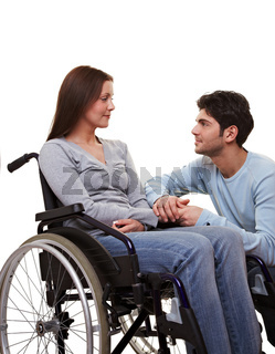 Mann tröstet Frau im Rollstuhl