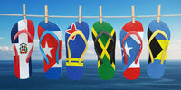 Hanging flip flops in colors of flags of different carribean countries Aruba, Bahamas, Cuba, Dominicana, Jamaica, Puerto-Rico. Travel and tourism concept.